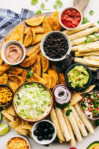 A taco board with dips and salsas with chips and tacos all around.