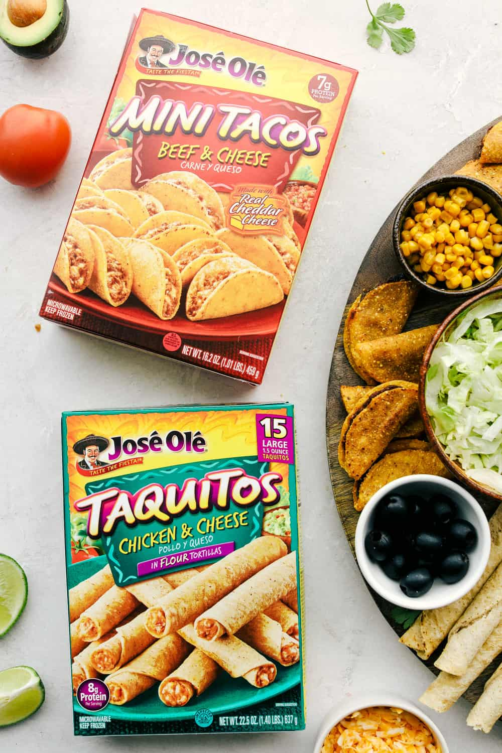 Mini tacos and taquitos in a box with the taco board on its side.