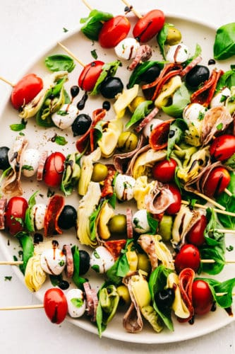 Antipasto skewers with cheese, olives, meats, spinach and cheese on a plate.
