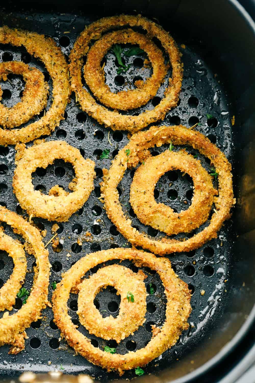 Air fryer onion rings in the air fryer basket.