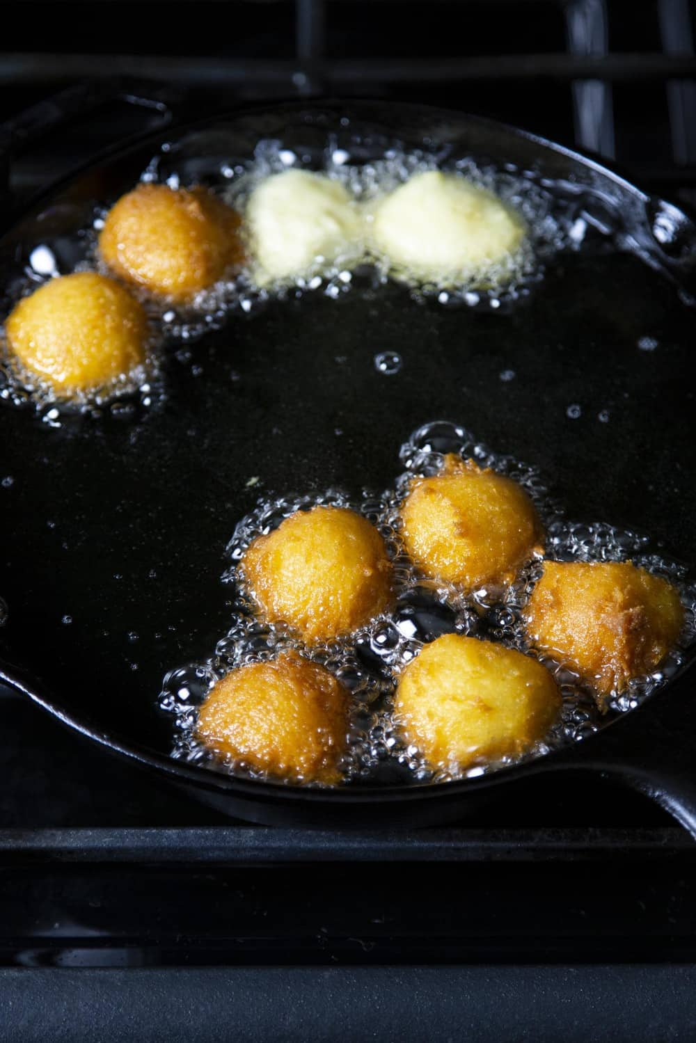 Donut holes frying in a pan of oil.