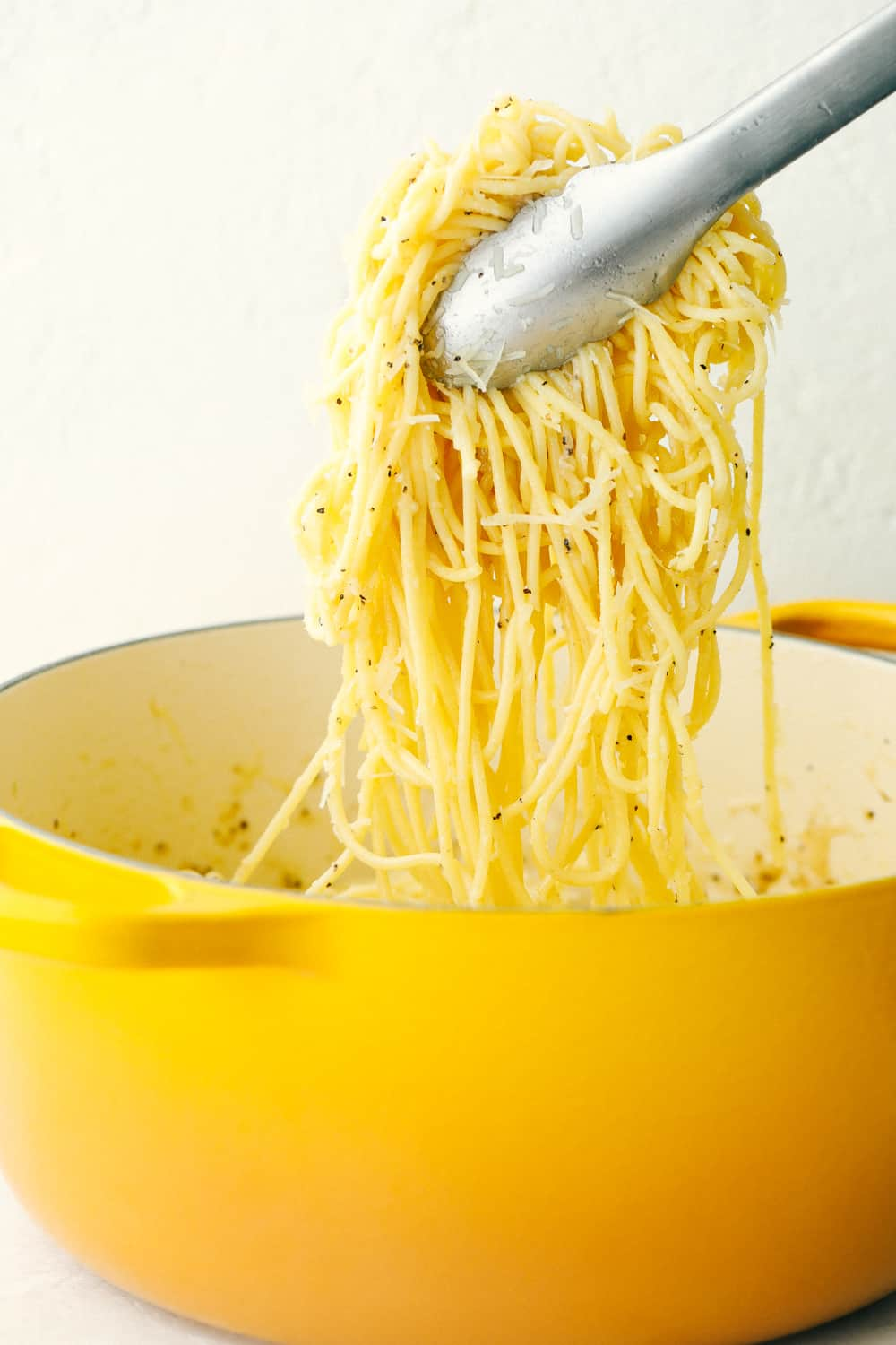 Hot noodles with Pecorino Romano Cheese and seasoning being lifted out of the pot with tongs.