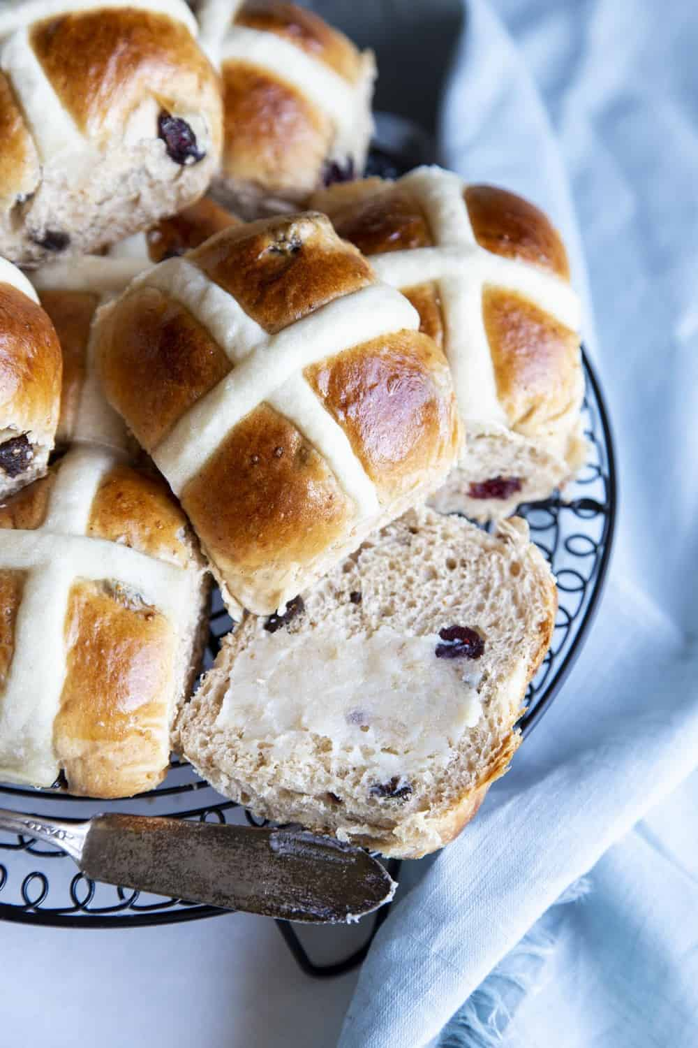 A plate of hot cross buns and one cut open with butter.