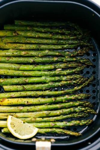 Air fryer roasted asparagus in an air fryer basket with lemon.