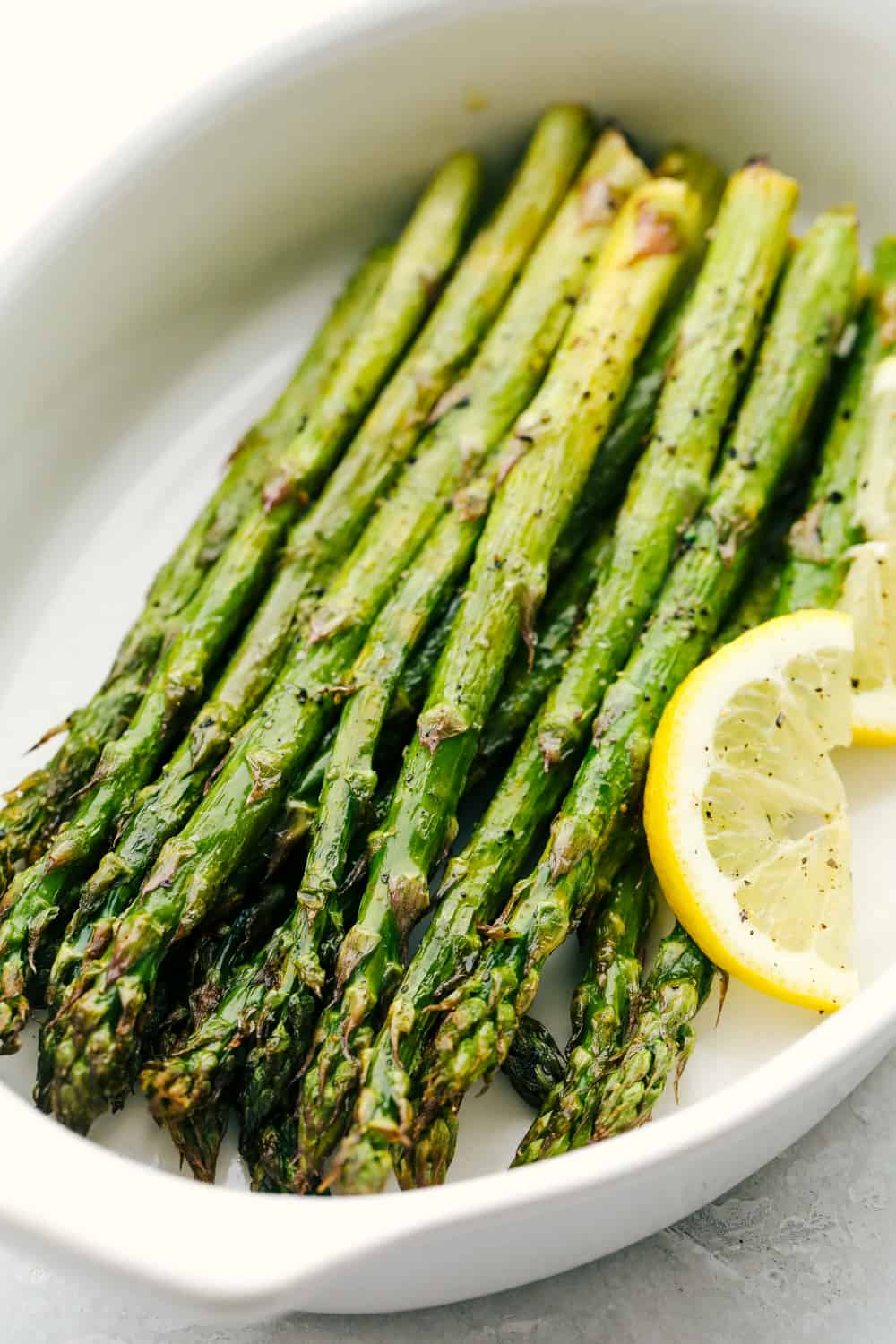 Air fryer roasted asparagus in a white dish.
