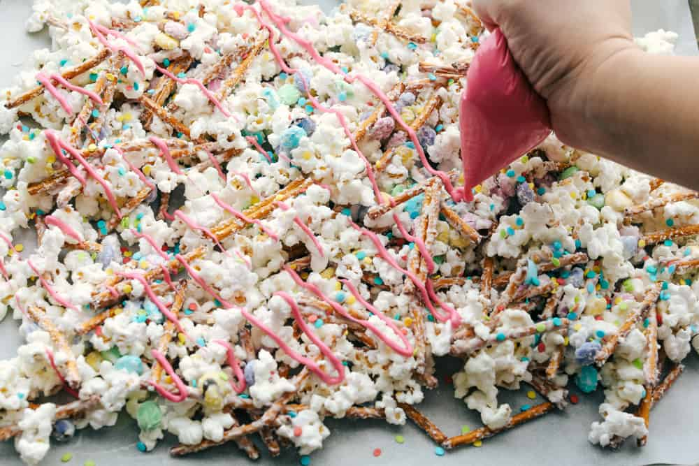 Adding colorful candy melt drizzles to the cooking popcorn mixture.