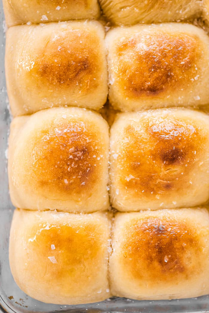 Potato buns in a baking pan with honey butter on top.
