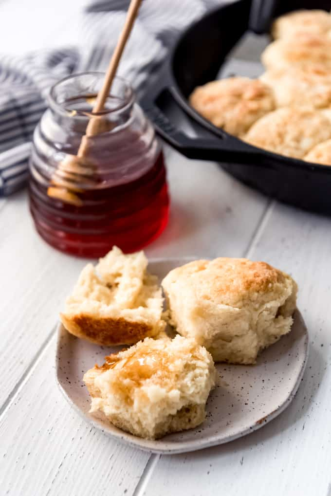 a biscuit on a plate with honey on it