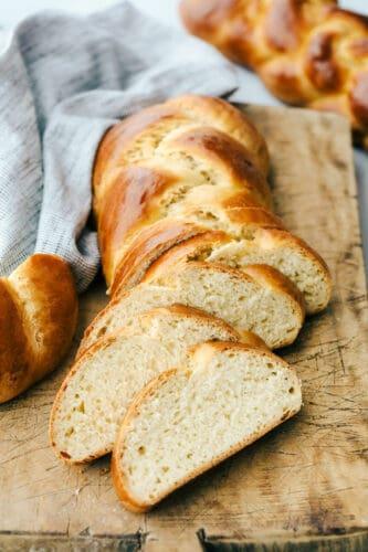 Sliced Challah on a breadboard.