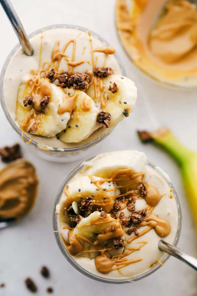 The top of a banana smoothie with fresh cut bananas with a straw in a glass cup.