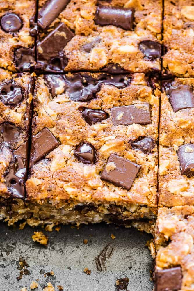Oatmeal chocolate chip bars in a baking dish with a few missing.