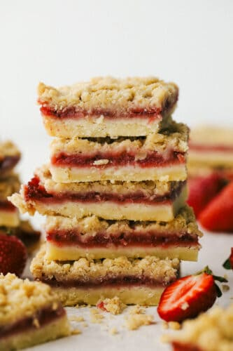 Strawberry streusel bars stacked on top of eachother ready to eat.