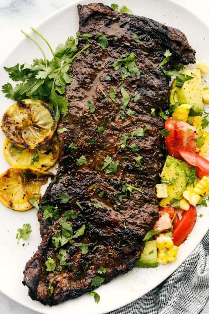 The grilled skirt steak whole on a plate with tomatoes, corn and tomatoes.