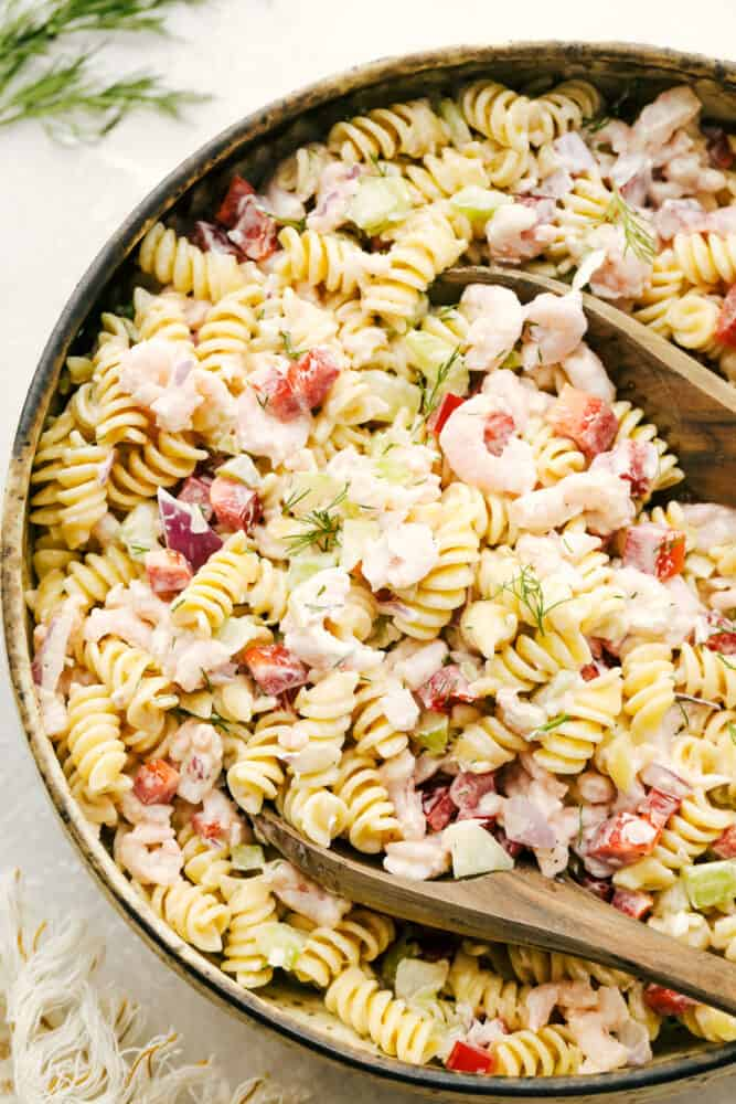 Shrimp pasta salad being mixed in a bowl