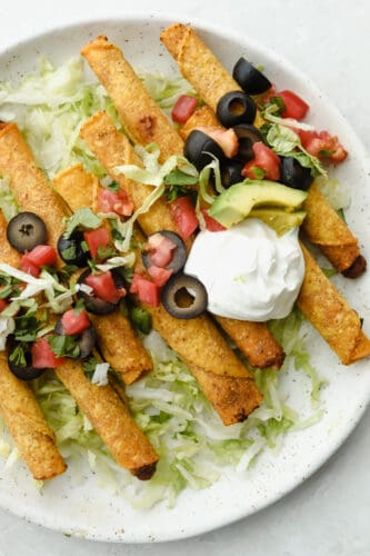 Air fryer taquitos on a white plate with sour cream, olives, tomatoes and lettuce.