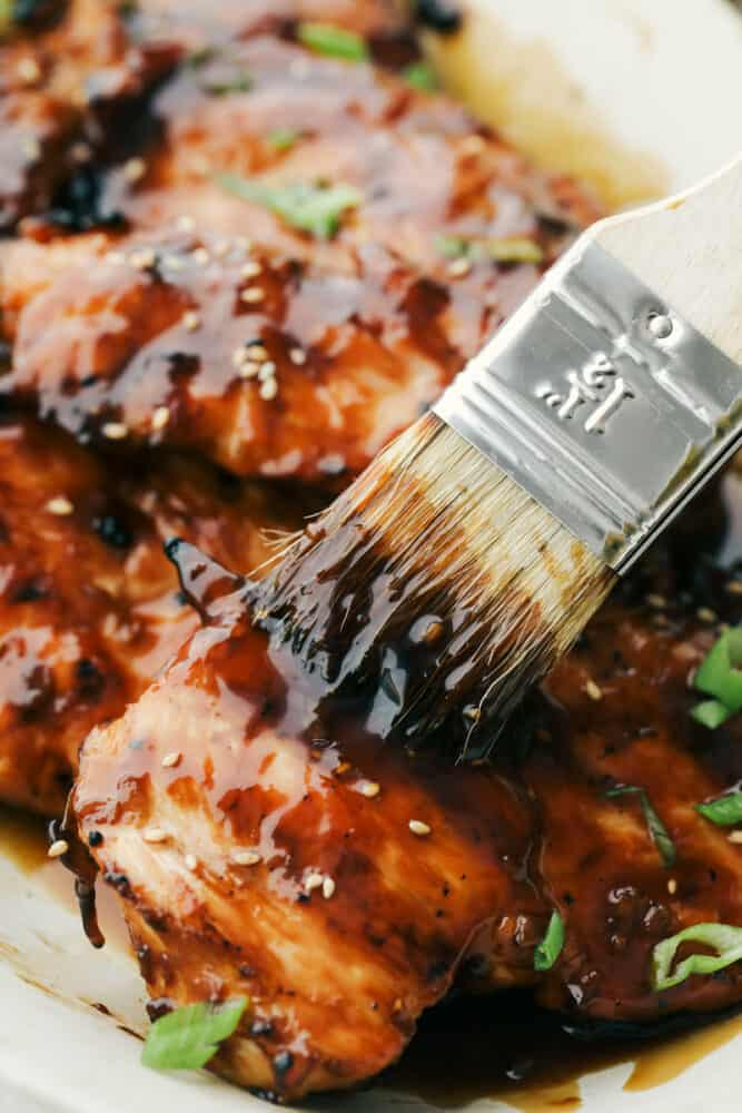 Basting the rest of the teriyaki sauce onto cooked chicken.