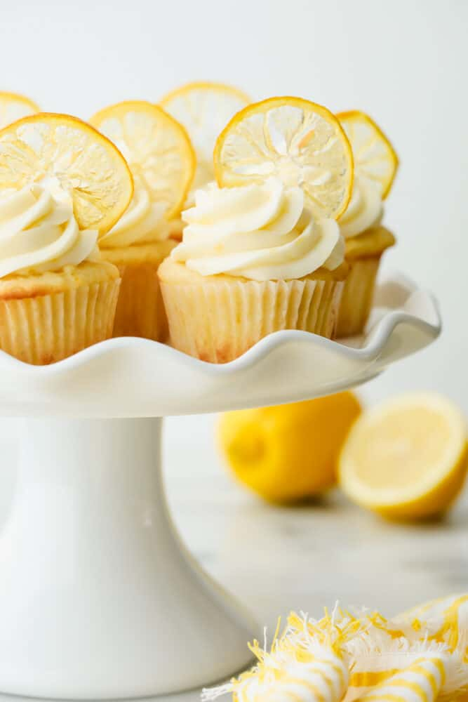 Lemon cupcakes with garnish on a serving platter.