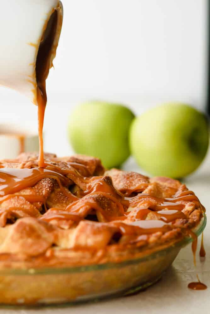 Pouring the caramel over the apple pie.