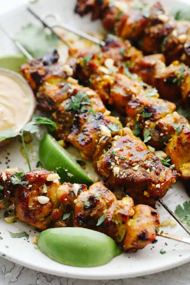 Chicken on skewers grilled with chopped peanuts for garnish.