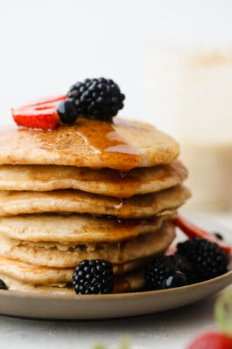 A stack of sourdough pancakes with berries on top.