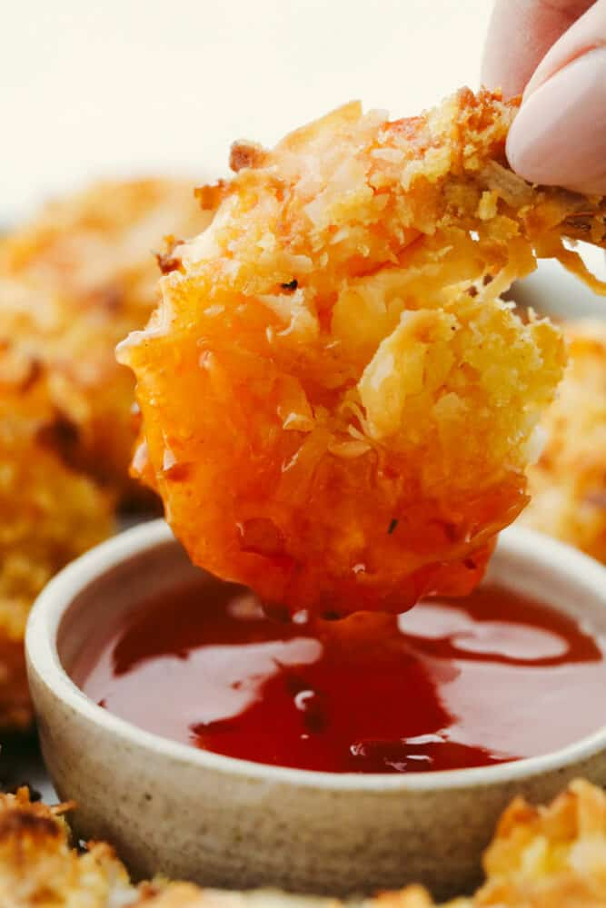 Baked Coconut Shrimp being dipped in sauce.