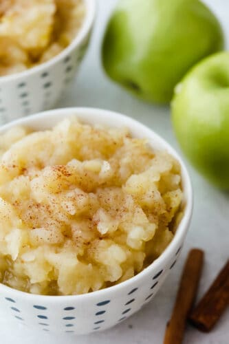 Applesauce in a bowl topped with cinnamon.