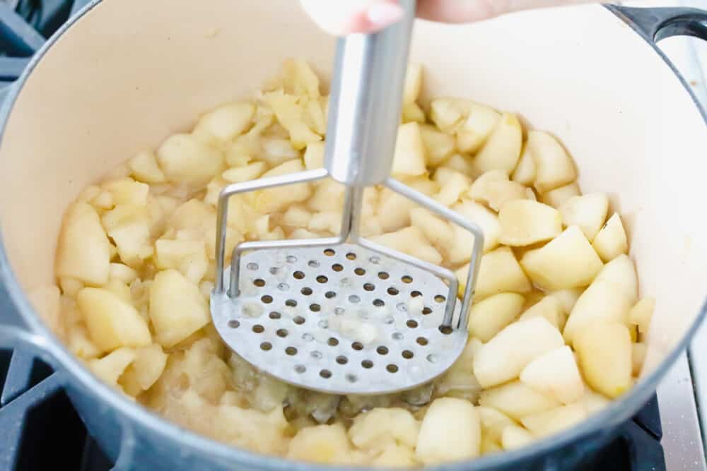Cooked apples being mashed up.