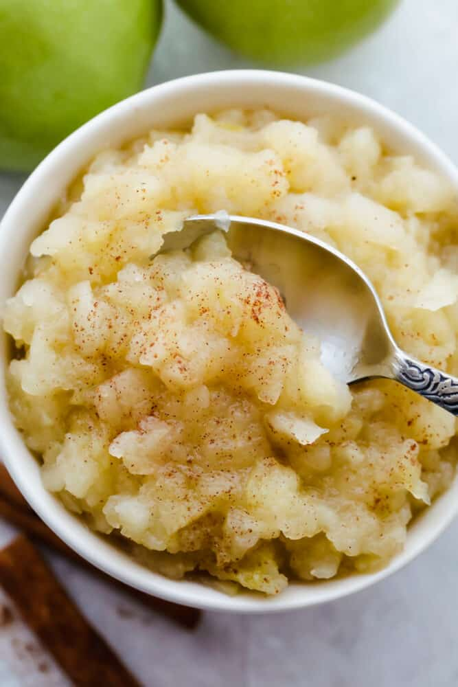 Finished homemade applesauce with spoon, ready to eat.