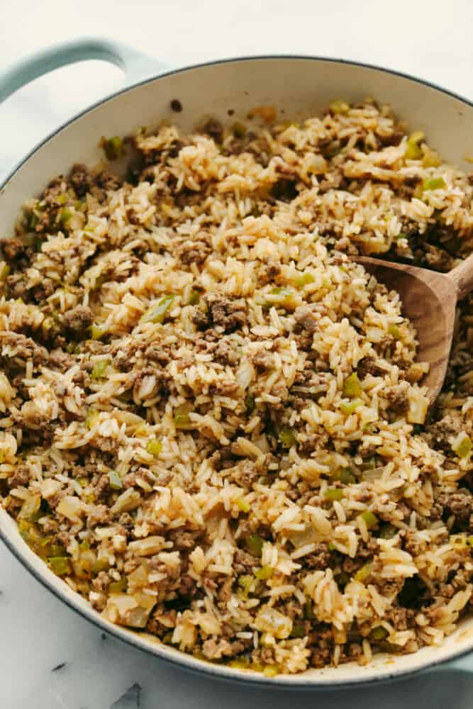 Rice with meat and veggies being served with a wooden spoon.