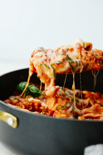 Skillet lasagna being served up with a large spoon.