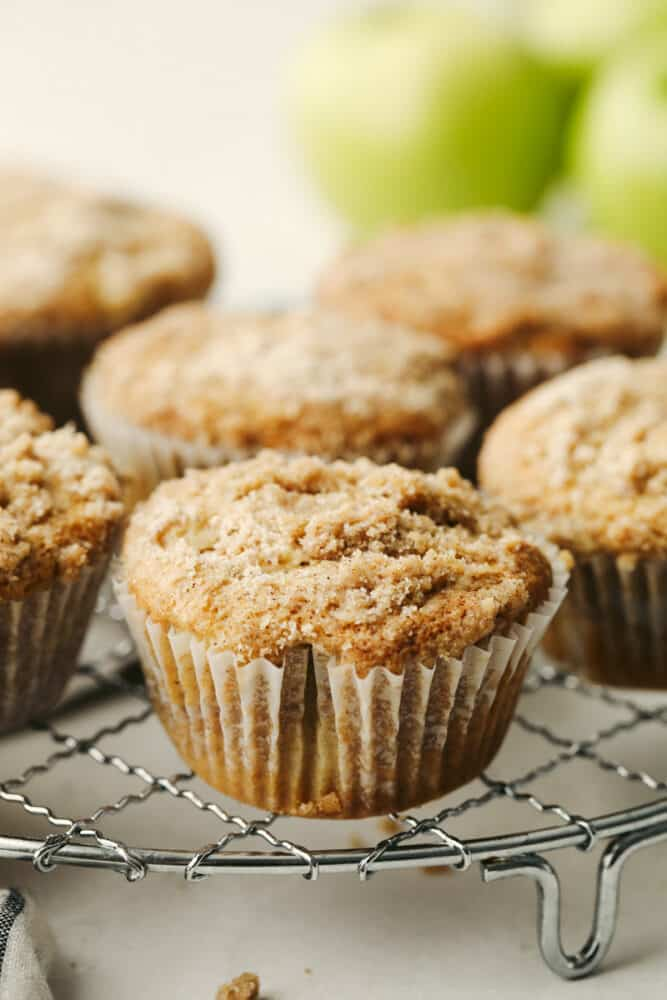 Apple streusel muffins on a wire rack.