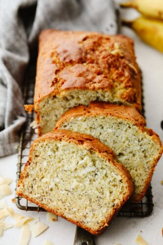 Sliced coconut banana bread on a cooling rack.