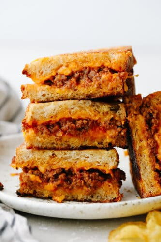 A sliced sloppy joe grilled cheese on a plate.