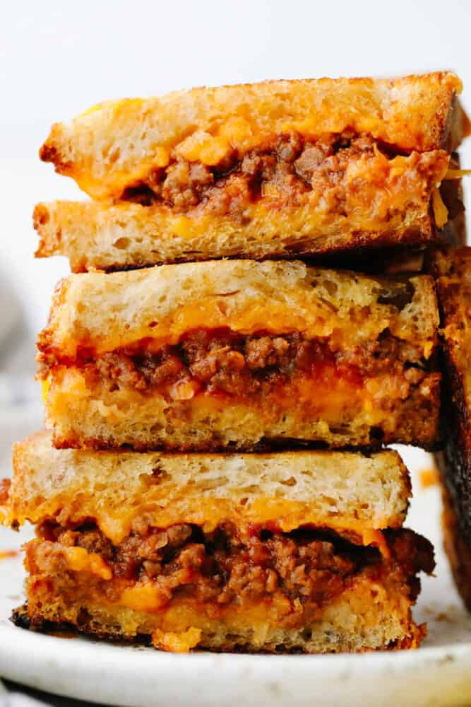 A stack of sliced sloppy joe grilled cheese sandwiches.