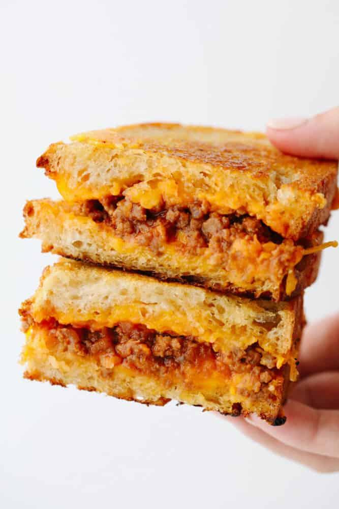 A hand holding 2 slices of a sloppy joe sandwich.