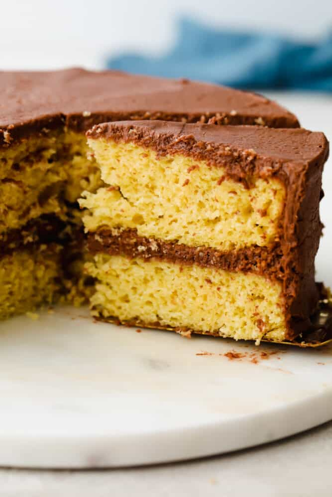 Yellow cake with chocolate frosting with a slice being pulled out.